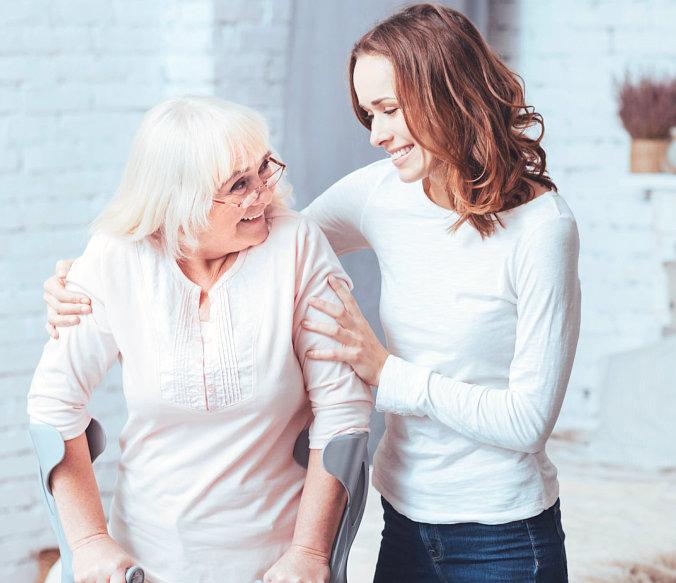 adult woman assting senior woman walking
