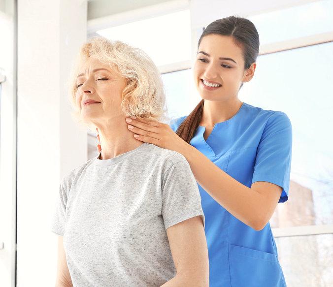 nurse assisting senior woman smiling