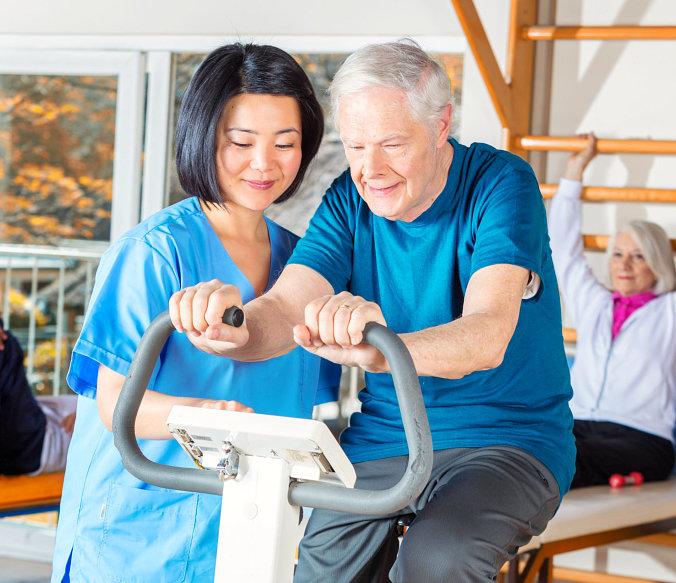 physician assisting senior man exercising