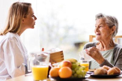 nurse talking with senior woman smiling