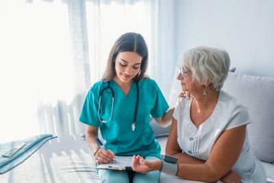 female nurse doing blood pressure monitoring for senior woman