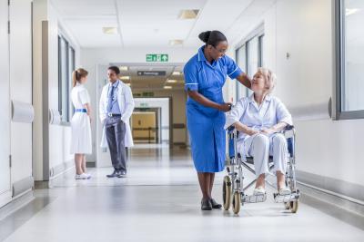 female nurse assisting a senior woman sitting in the wheelchair