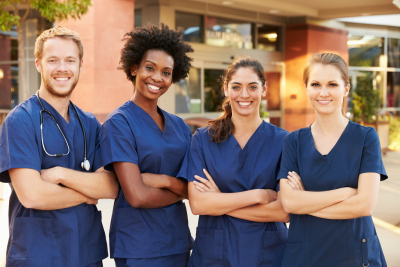 a group of nurse standing outside of the hospital smiling